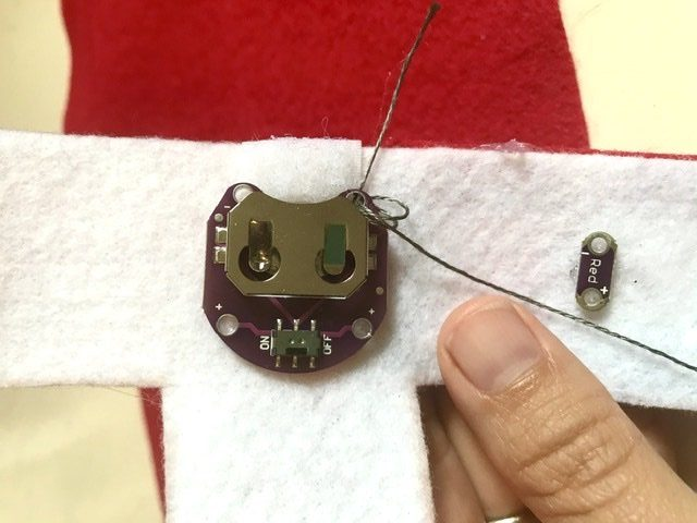 Sewing down the battery with thread going through negative hole